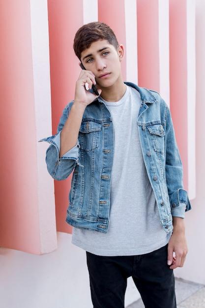Bonito, menino adolescente, falando, ligado, telefone móvel, ficar, frente, parede cor-de-rosa Foto gratuita