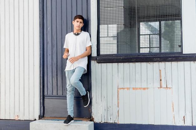 Bonito, menino adolescente, inclinar-se, corrugated, ferro, tapume, olhando câmera Foto gratuita