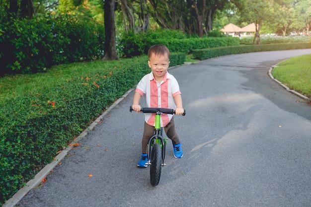 Bonito menino ásia criança aprendendo a andar de bicicleta de primeiro equilíbrio em dia ensolarado de verão, criança brincando e andar de bicicleta no parque Foto Premium