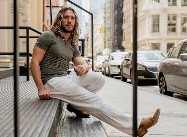 Bonito modelo masculino posando na escada Foto gratuita
