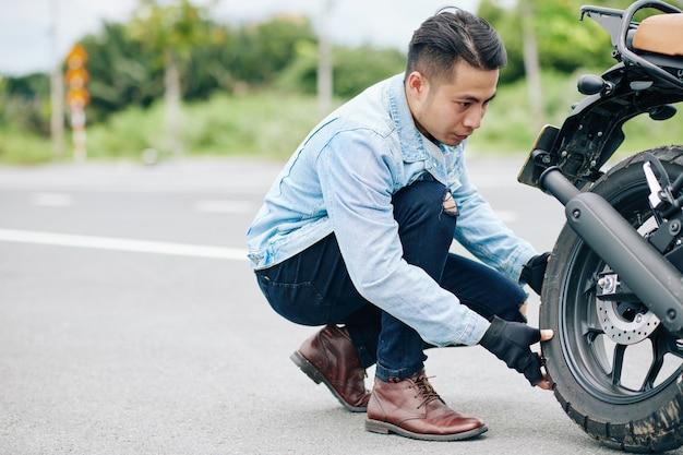 Bonito motociclista vietnamita sério tirando o pneu de sua moto para bombeá-la Foto Premium