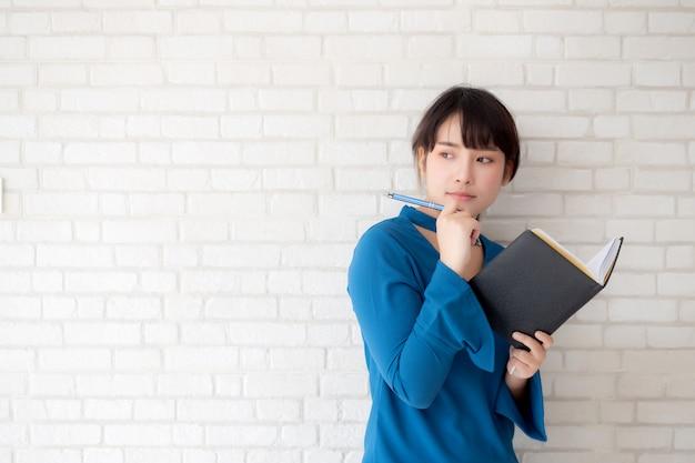 Bonito, mulher asian, sorrindo, ficar, pensando, e, escrita, caderno, ligado, concreto, cimento, fundo branco Foto Premium