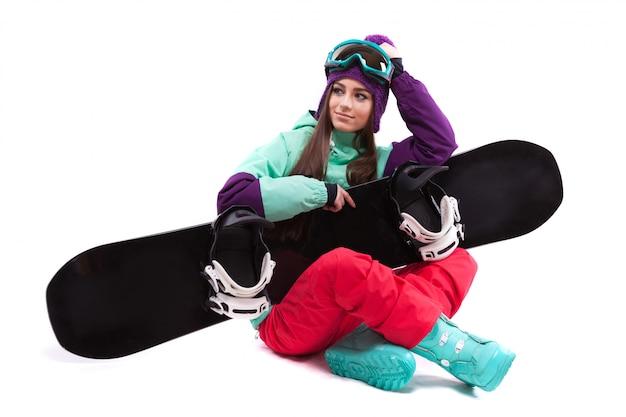 Bonito, mulher jovem, em, roxo, traje esqui, localização, de pernas cruzadas Foto Premium