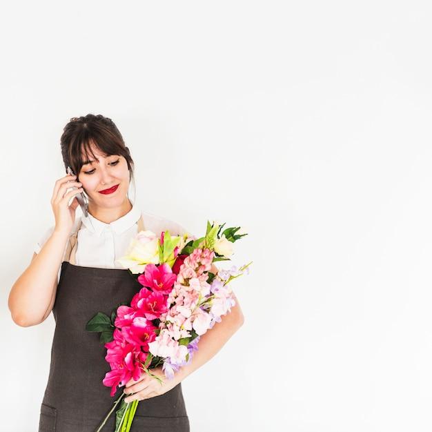 Bonito, mulher jovem, falando telefone móvel, segurando, grupo flores Foto gratuita
