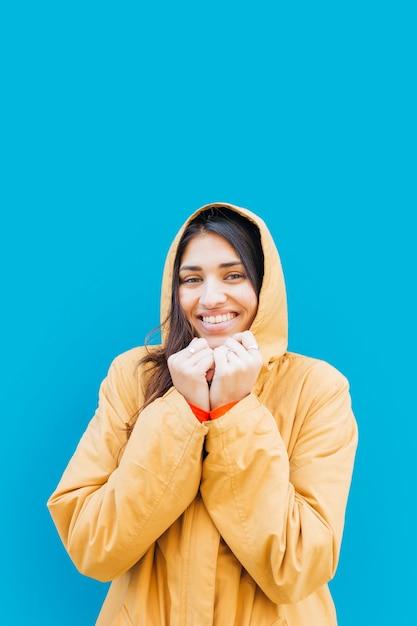 Bonito, mulher jovem, olhando câmera, em, frente, experiência azul Foto gratuita