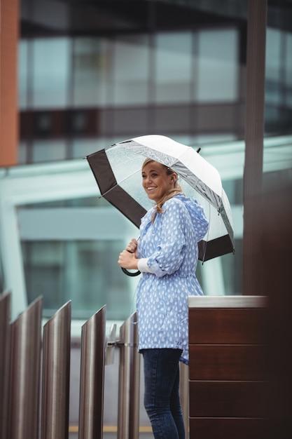 Bonito, mulher segura, guarda-chuva, e, ficar, ligado, rua Foto gratuita