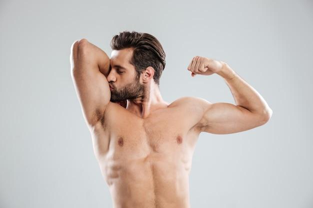 Bonito nu jovem mostrando e beijando seu bíceps Foto gratuita