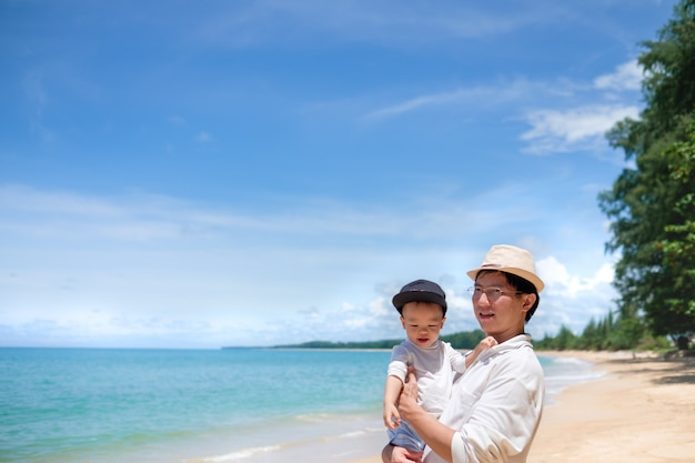 Bonito pequeno asiático 1 ano de idade / 18 meses criança bebê menino brincar com o pai na praia de areia branca Foto Premium