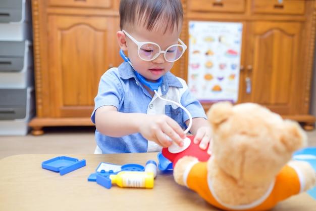 Bonito pequeno asiático 2 anos de idade criança menino criança brincando de médico com brinquedos de pelúcia em casa, garoto segurando o estetoscópio examinar o ursinho de pelúcia brinquedo Foto Premium