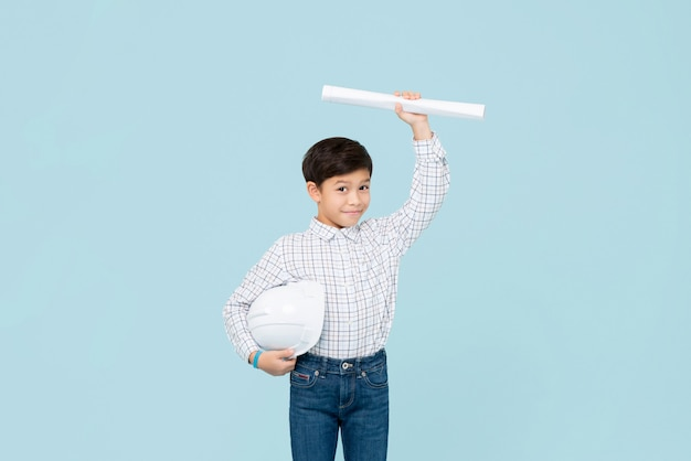 Bonito rapaz asiático sorridente com capacete, aspirando a ser o futuro engenheiro, mostrando a planta isolada na parede azul clara Foto Premium
