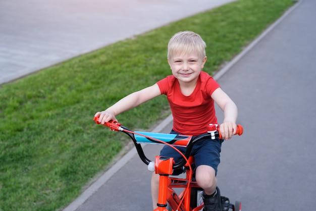 Bonito rapaz loiro passeios de bicicleta infantil Foto Premium