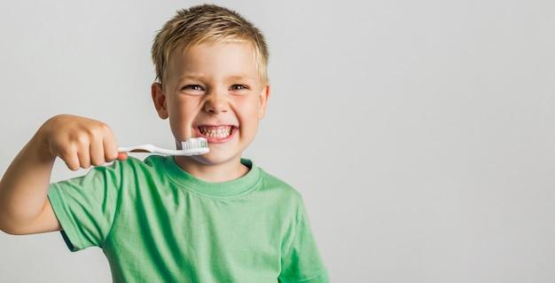 Bonito rapaz segurando a escova de dentes Foto gratuita