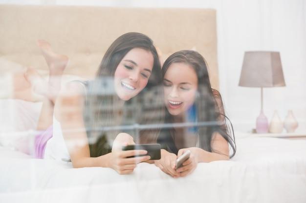 Bonitos amigos olhando para smartphone na cama Foto Premium