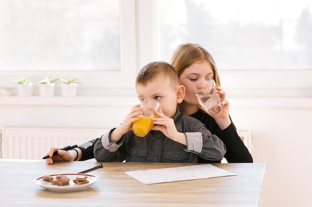 Bonitos criancinhas bebendo água e suco em casa ou berçário Foto Premium