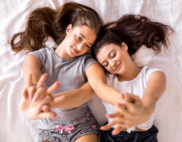 Bonitos mulheres com as mãos para cima na cama Foto gratuita