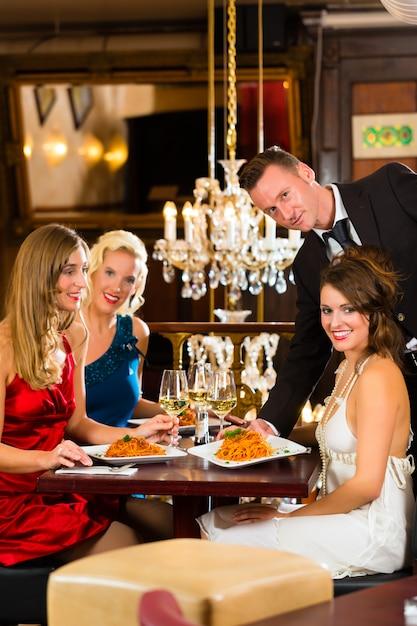 Bons amigos para almoçar em um restaurante fino, garçom serviu o jantar Foto Premium
