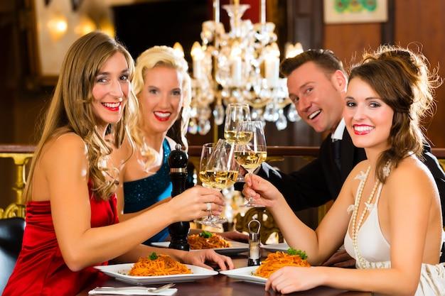 Bons amigos para jantar ou almoçar em um bom restaurante, copos tilintando Foto Premium