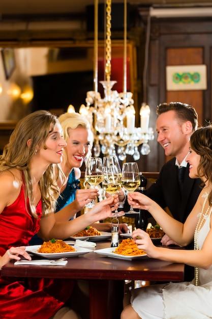 Bons amigos para jantar ou almoçar em um restaurante fino, tilintar de copos Foto Premium