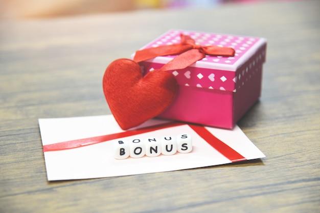 Bônus de cartão em envelope de papel com surpresa de caixa de presente e coração vermelho Foto Premium