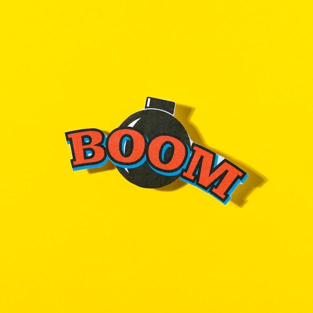 Boom cômico texto balão com bomba em fundo amarelo Foto gratuita