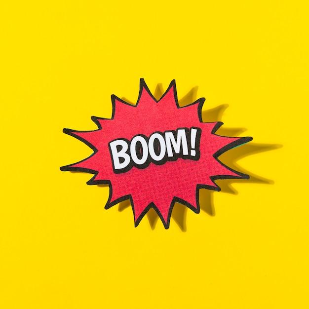 Boom da palavra! na bolha do discurso em quadrinhos retrô em fundo amarelo Foto gratuita