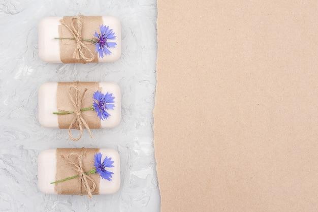 Borda de conjunto de sabonete natural artesanal, decorada com papel ofício, flagelo e flores azuis no backgrouniew de pedra cinza Foto Premium