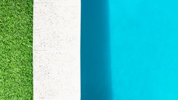 Borda de grama, borda de pedra e água da piscina Foto gratuita