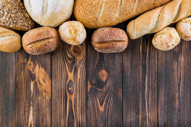 Borda superior feita com pães diferentes na tábua de madeira Foto gratuita