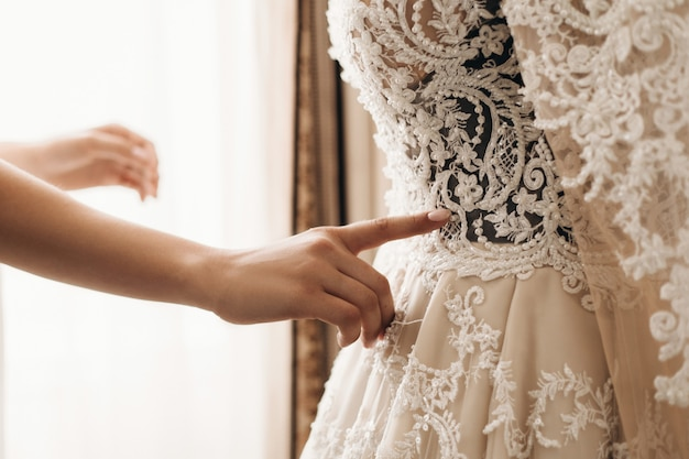 Bordado no lindo vestido de noiva, preparando-se para a cerimônia de casamento, vestido artesanal de alta costura Foto gratuita