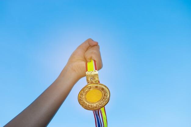 Borrada de mãos de mulher levantadas e segurando medalhas de ouro com fita tailandesa contra fundo de céu azul para mostrar sucesso em esporte ou negócios, winners sucesso conceito de prêmio. Foto Premium