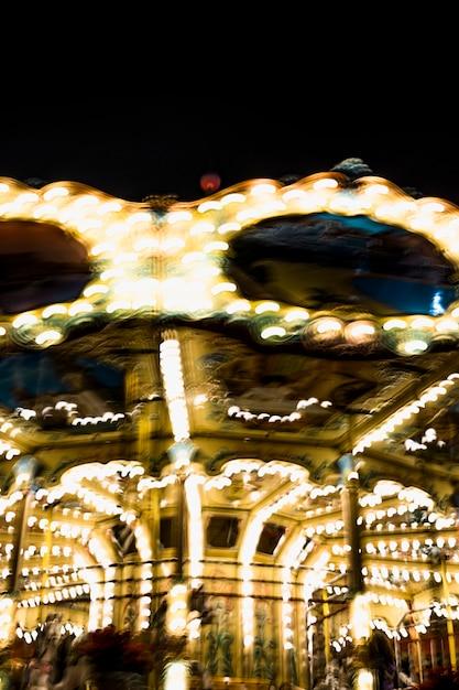 Borrão de iluminação do carrossel está girando no parque de diversões na noite Foto gratuita