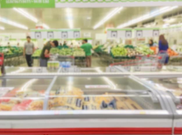 Borrão de movimento de prateleiras de frutas à venda no supermercado com algumas pessoas compras Foto Premium