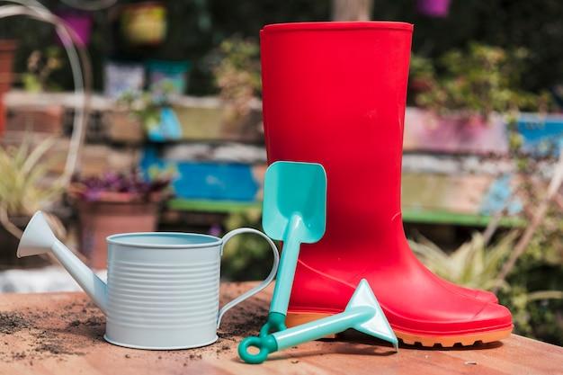 Bota de borracha vermelha; pá azul e regador na mesa no jardim Foto gratuita