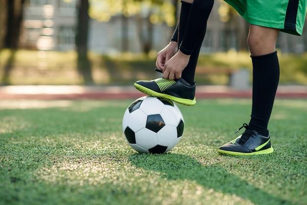 Bota de jogador de futebol em uma bola. rapaz amarrando o cadarço no estádio de futebol. Foto Premium