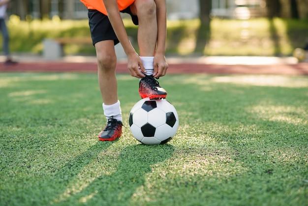 Bota de jogador de futebol que coloca a perna na bola e amarrando o cadarço. Foto Premium