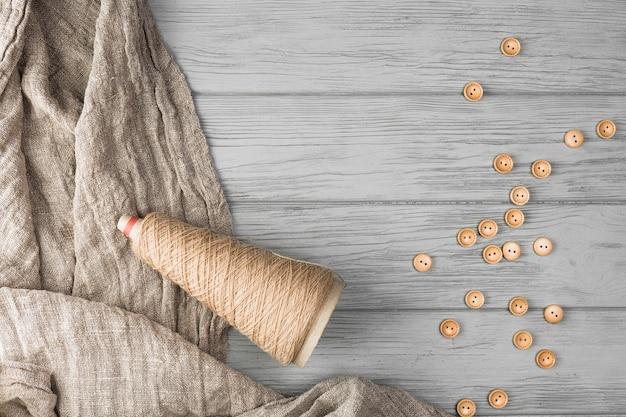 Botão marrom; carretel de corda e pano no plano de fundo texturizado de madeira Foto gratuita