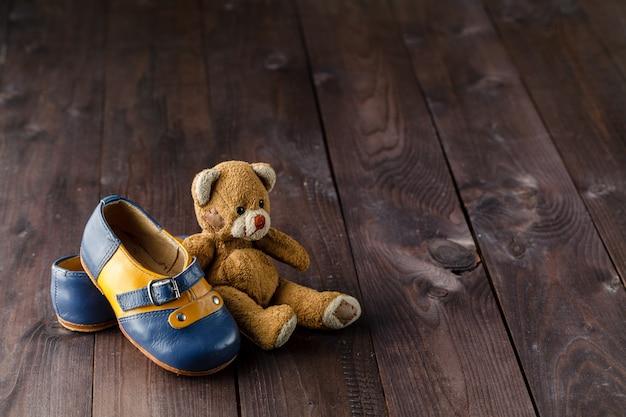 Botas de bebê na mesa de madeira sobre a superfície do grunge de parede, estilo vintage Foto Premium