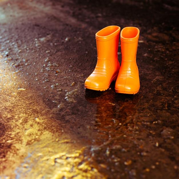 Botas de borracha laranja em pé ao lado da poça. Foto Premium