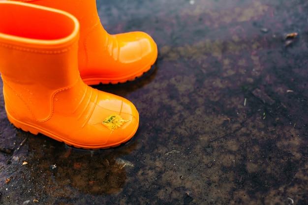Botas de borracha laranja em pé em uma poça Foto Premium