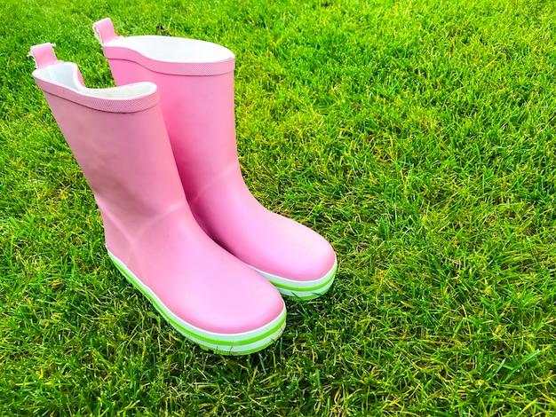 Botas de borracha rosa ficar na grama verde. Foto Premium