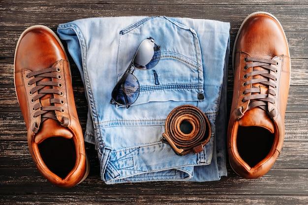 Botas de couro marrom, cinto, óculos de sol e jeans azul Foto Premium