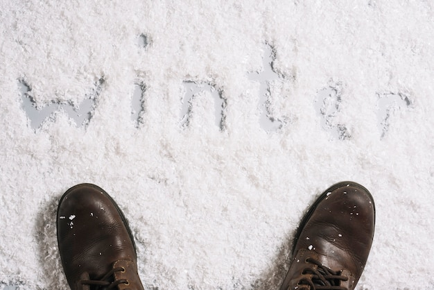 Botas perto de título de inverno na superfície de neve Foto gratuita