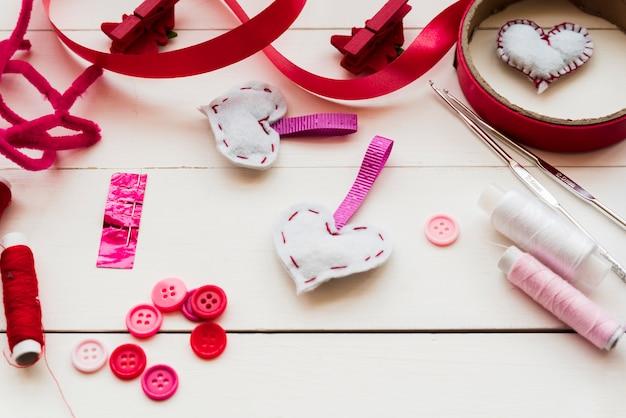 Botões; agulhas de crochet; bobinas de fio; fitas para costura forma de coração de tecido na mesa de madeira Foto gratuita