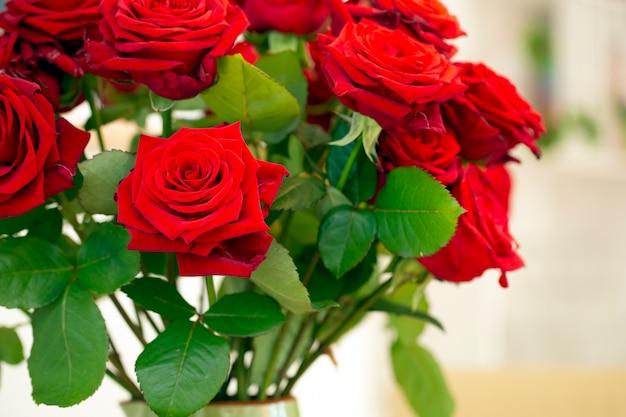 Bouquet de lindas rosas vermelhas em um vaso verde sobre fundo colorido em casa aconchegante, conceito de dia dos namorados Foto Premium