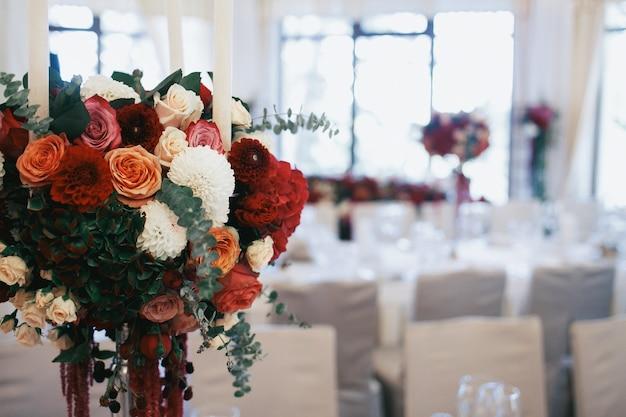 Bouquet de rosas e alfinete fica na mesa do jantar no restaurante Foto gratuita
