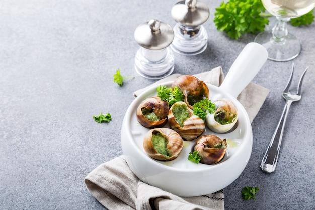 Bourgogne escargot caracóis com manteiga de ervas de alho em panela branca Foto Premium