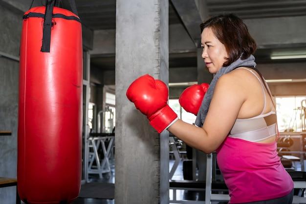 Boxe gordo asiático sênior do treinamento da mulher no gym da aptidão. Foto Premium