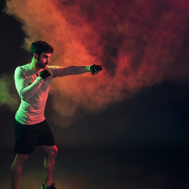Boxer confiante em fumo escuro no estúdio Foto gratuita
