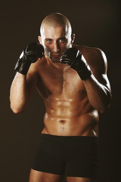 Boxer em um rack com um belo corpo musculoso e careca Foto gratuita