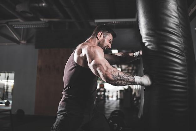 Boxer masculino treinando com saco de pancadas no salão de esportes escuro Foto Premium
